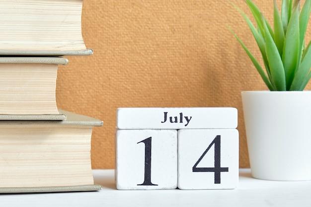 Концепция календаря месяца 14-ое июля четырнадцатого дня на деревянных блоках. Premium Фотографии