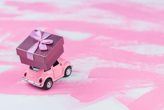 Розовый ретро игрушечный автомобиль поставляет подарочную коробку на розовом фоне. открытка 14 февраля, день святого валентина. доставка цветов. женский день Premium Фотографии