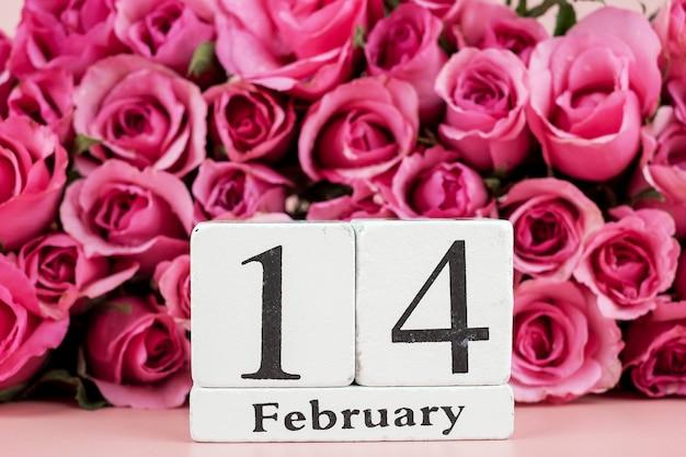 Розовый цветок розы и 14 февраля календарь на розовом фоне. любовь, романтика и счастливый день святого валентина концепция праздника Premium Фотографии