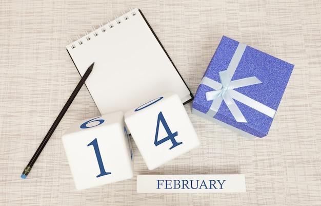 Календарь с модным синим текстом и цифрами на 14 февраля и подарком в коробке. Premium Фотографии