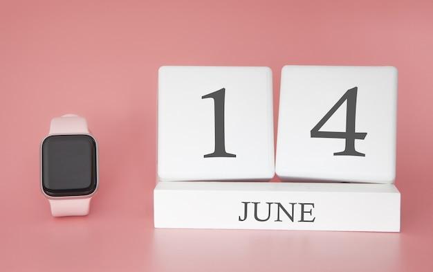 Умные часы с кубическим календарем и датой 14 июня на розовом столе. Premium Фотографии