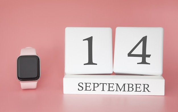 Современные часы с кубическим календарем и датой 14 сентября на розовой стене. концепция осеннего времени отдыха. Premium Фотографии