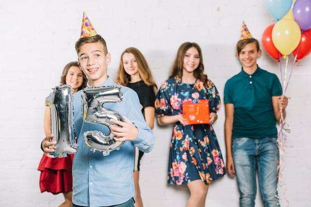 友人の前に立っている灰色の番号15ホイルバルーン番号を保持している10代の少年 無料写真