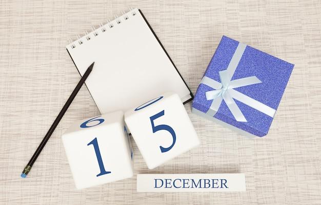 Кубический календарь на 15 декабря и подарочная коробка, рядом блокнот с карандашом Premium Фотографии
