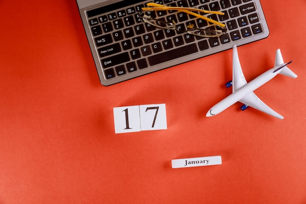17 january calendar with accessories on business workspace office desk on computer keyboard, airplane, glasses red background Premium Photo