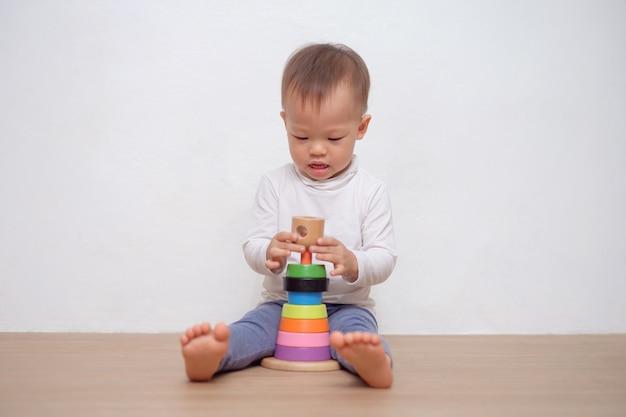 かわいい小さなアジア18ヶ月/ 1歳の幼児男の子男の子カラフルな木製のピラミッドのおもちゃ/スタッキングリングおもちゃで遊ぶ。コピースペースの白い壁に分離された教育おもちゃで遊ぶ子供 Premium写真