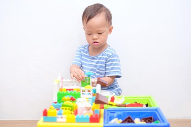 かわいい小さなアジア18ヶ月、1歳の幼児男の子の子供が木の床に座って楽しんでカラフルなビルディングブロックを自宅で屋内で遊んで、幼児の概念のための教育おもちゃ Premium写真
