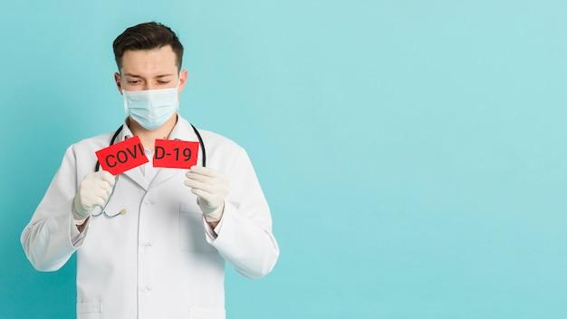 Заинтересованный доктор, разрывающий карточку ковид-19 Бесплатные Фотографии