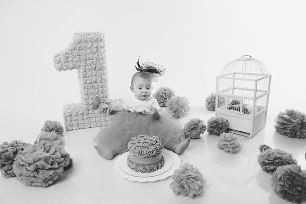 誕生日のお祝い:数字1の間で床に座っている女の子、造花、鳥かご Premium写真