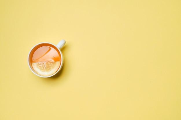 黄色い紙の背景にレモン入り紅茶1杯。上面図。 Premium写真