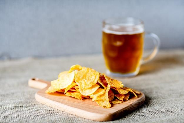 グラス1杯のビール、グレーの塩味のチップ Premium写真