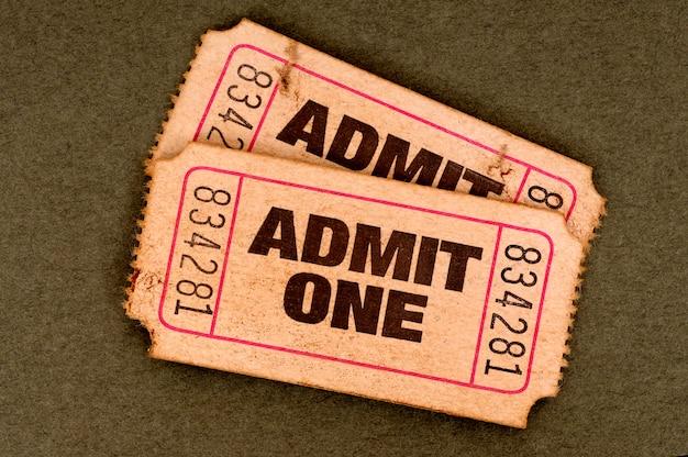 引き裂かれた昔のペアは、茶色の背景に1つの映画のチケットを認める。 無料写真
