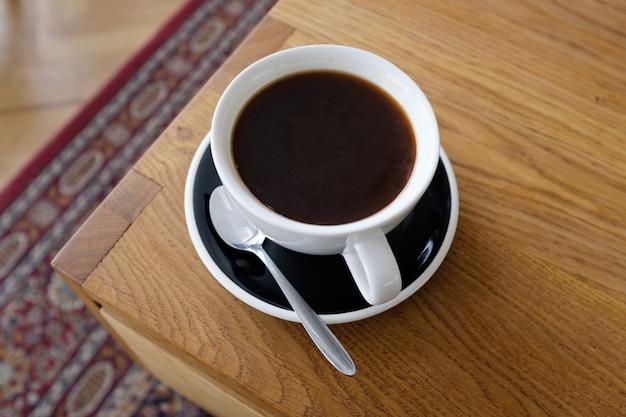 木製のテーブル、朝のコーヒーに黒いコーヒー1杯。 Premium写真