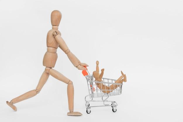 買い物中毒。別の1つに座っているショッピングカートに乗って木製の男。白で隔離 Premium写真