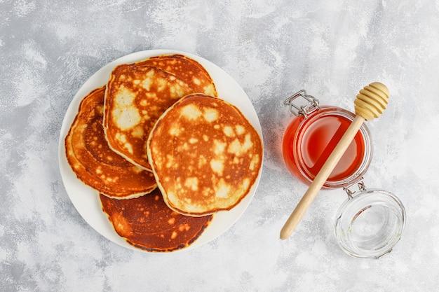 自家製の朝食:洋ナシと蜂蜜を添えたアメリカンスタイルのパンケーキ、コンクリートの上にお茶を1杯。トップビューとコピー 無料写真