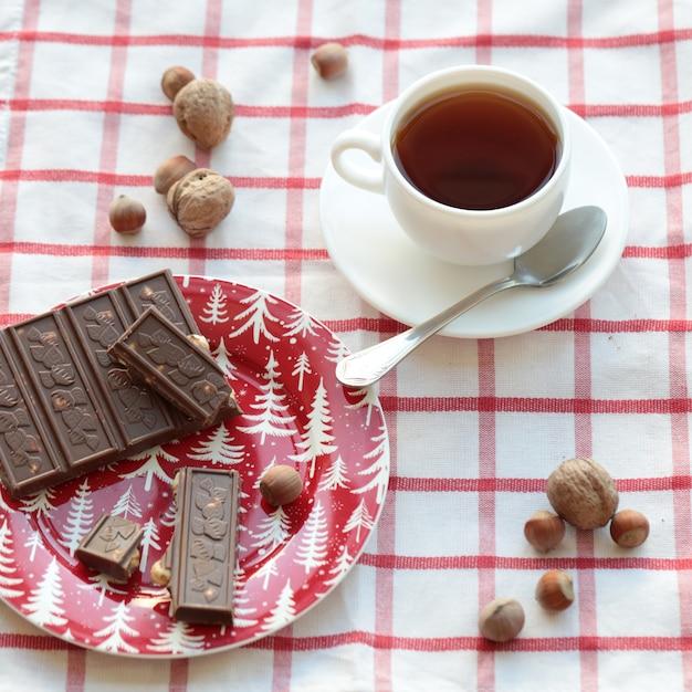 チェックタオルの上にチョコレートバーとお茶を1杯。 無料写真