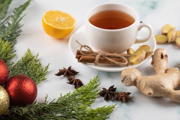 クリスマスにシナモン、レモン、ジンジャーとお茶を1杯装飾された大理石のテーブル。 無料写真