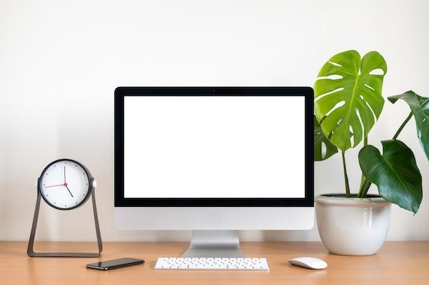 1台のコンピューター、キーボード、マウス、モンステラ植木鉢、木製のテーブルの時計のすべての空白の画面 Premium写真