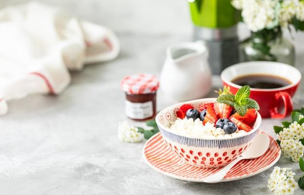 ベリー、ジャム、新鮮なイチゴ、朝食用クリーム入りコーヒー1杯入りのカッテージチーズ。 Premium写真
