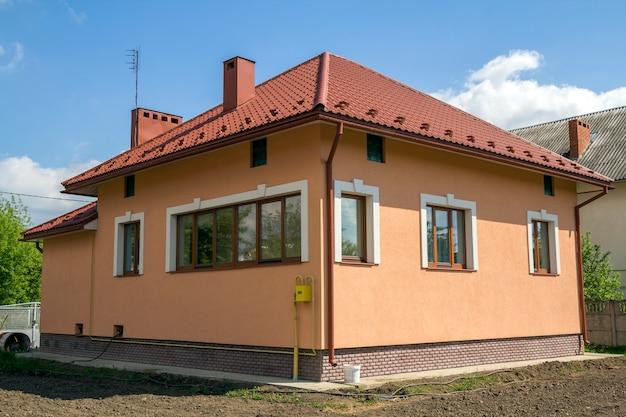 赤いタイル張りの屋根、プラスチックの窓、漆喰の壁、静かな近所のフェンスで囲まれた土地の高い煙突を備えた、新しく建てられた1棟のコテージ。建設と不動産のコンセプト。 Premium写真
