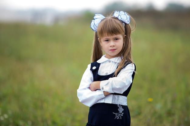 学校の制服を着たかわいい愛らしい自信を持って1年生の女の子と長いブロンドの髪に白い弓のクローズアップの肖像画。 Premium写真