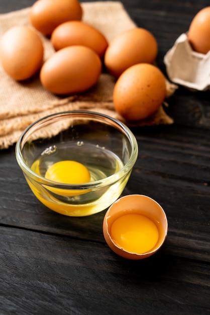 1つの壊れた卵の黄身と茶色の卵 Premium写真