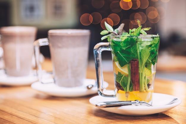 ミント、シナモン、白い皿のレモン入り紅茶1杯 Premium写真