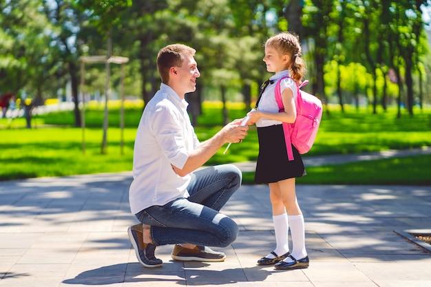 父は1年生で娘を学校に連れて行きます。学校の初日。学校に戻る。 Premium写真
