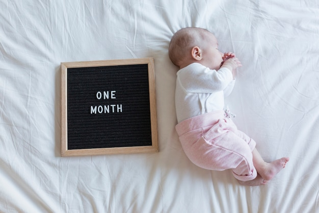 自宅で白い背景の美しい赤ちゃんの肖像画を間近します。レターボードヴィンテージ1ヶ月のメッセージ Premium写真