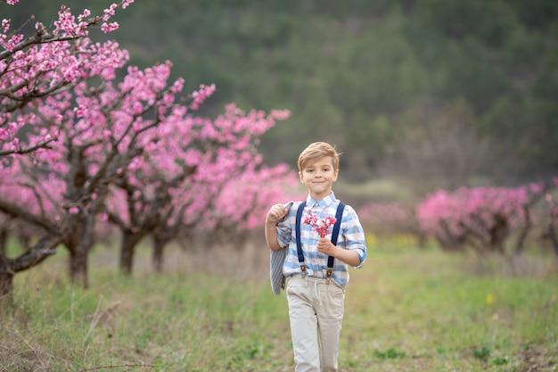 サスペンダー付きパンツで陽気なかわいい男の子1年生が春の庭を歩く Premium写真