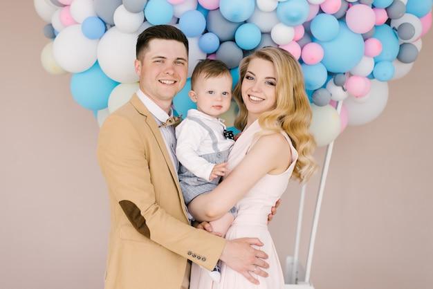 美しい若い両親は、ピンクとブルーの風船で1歳の子供と笑います。家族の外観。ハッピーバースデーパーティー Premium写真
