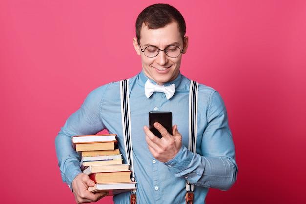本のスタック、1つのトーンの服を着たシャツ、サスペンダー、蝶ネクタイで学生を笑顔 Premium写真