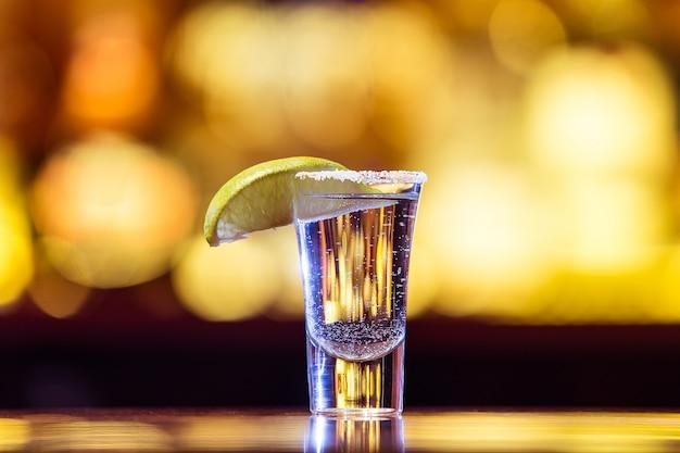 明るいライトのガラスの1つのシルバーテキーラ。伝統的なメキシコの飲み物。 Premium写真