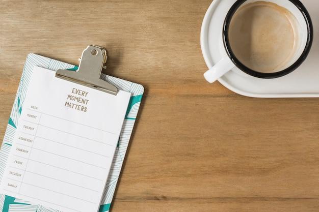 木製の机のクリップボードとコーヒーの1週間の計画 無料写真