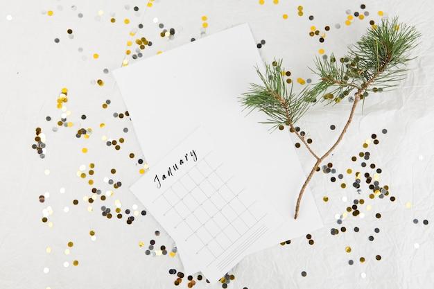 テーブルに1月のカレンダーが付いているモミの木ブランチ 無料写真