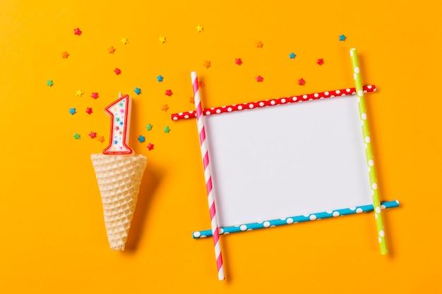 Свеча номер 1 с разноцветной звездой посыпает вафельный рожок и пустую рамку на оранжевом фоне Бесплатные Фотографии