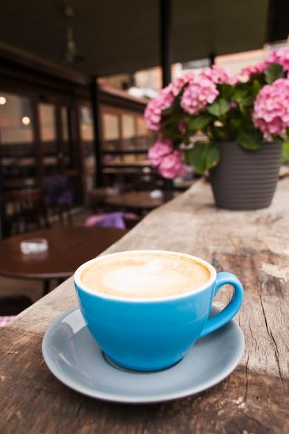 空のカフェで古い木製の織り目加工テーブルの上にコーヒーを1杯 無料写真