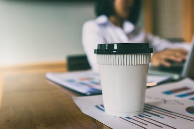 実業家の背景を持つレポート用紙にコーヒー1杯。 Premium写真