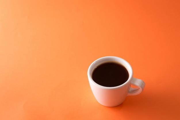 オレンジ色の背景上のコーヒー1杯 Premium写真
