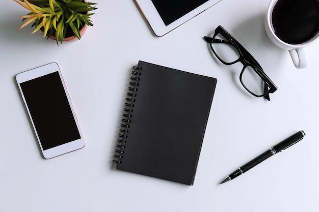 空の画面スマートフォンとコピースペースを備えたビジネスデスクオフィスのコーヒー1杯とタブレット Premium写真