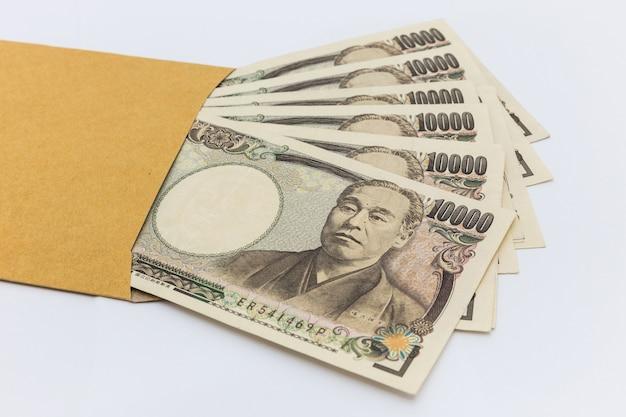 日本銀行1万円、贈り物とビジネス成功と買い物のための茶色の封筒。 Premium写真