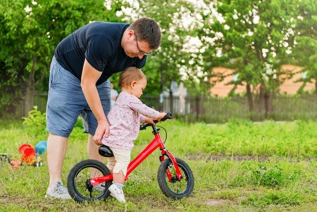 若い父親は、かわいい小さな1歳の幼児の女の子子供とバランスバイクと過ごす Premium写真