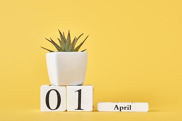 Календарь деревянных блоков с датой 1-ое апреля и завод на желтой предпосылке. апрельский день дураков Premium Фотографии