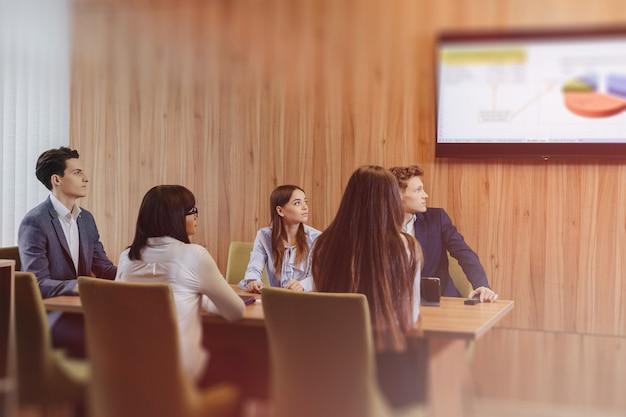 人々の大規模なチームは、ラップトップ、タブレット、ペーパー用の1つのテーブルで働いており、背景には木製の壁に設置された大きなテレビ Premium写真