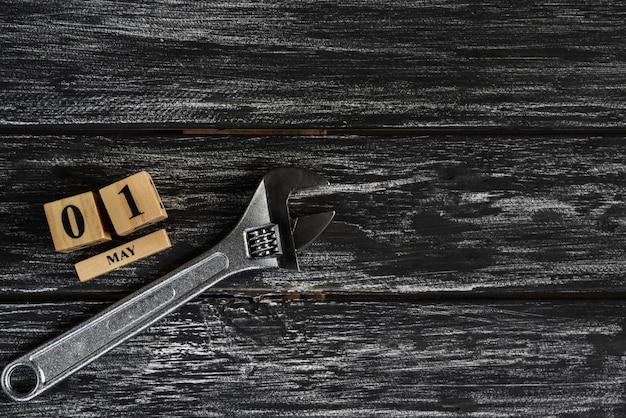 1 мая текст деревянный блок календарь и разводной ключ на черном фоне деревянные. Premium Фотографии