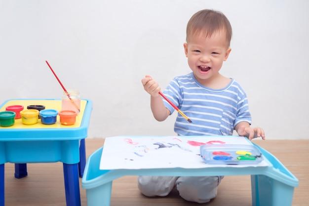 かわいいアジアの1歳の幼児の男の子の子供が自宅でブラシと水彩で絵を描く、身体発達のための創造的な芸術活動、子供の大小の筋肉発達の概念 Premium写真