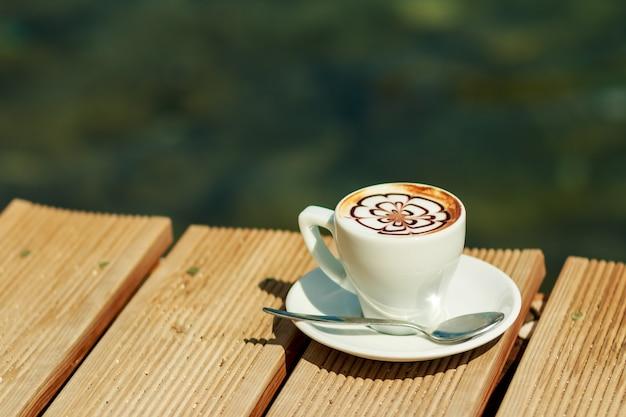 コーヒー、カプチーノ、ラテアート、ラテ。プロのコーヒー1杯が分離されました。温かい飲み物の素晴らしいカップ。 Premium写真