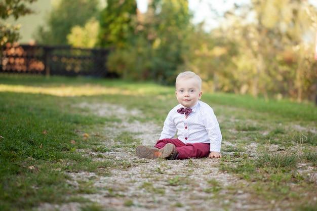 かわいい遊び心のある笑顔の金髪。緑の芝生の上に座っている1歳の少年。 Premium写真