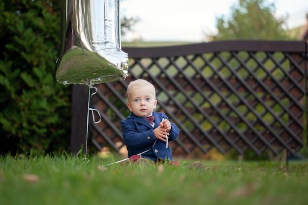かわいい遊び心のある笑顔の金髪。夏の日の屋外の緑の芝生の上に座っている1歳の男の子。 Premium写真