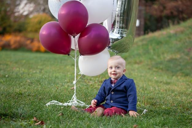 かわいい遊び心のある笑顔の金髪。日当たりの良い夏の日の屋外の緑の芝生の上に座っている1歳の男の子。 Premium写真